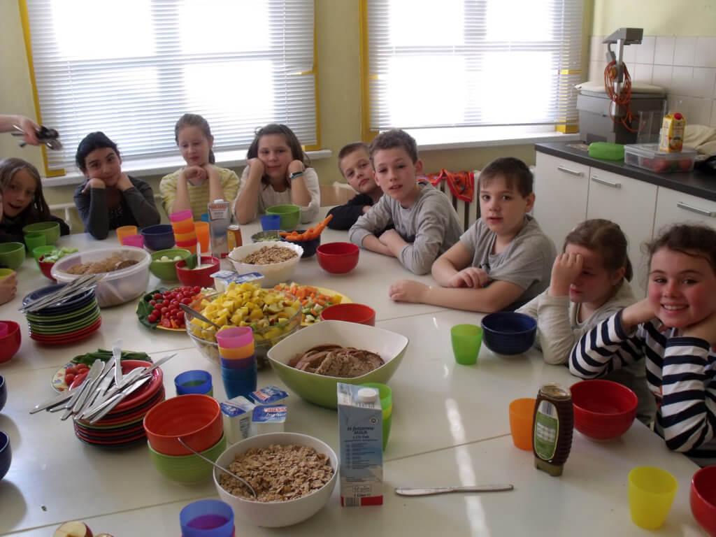 Schüler sitzen an einem gedeckten Tisch